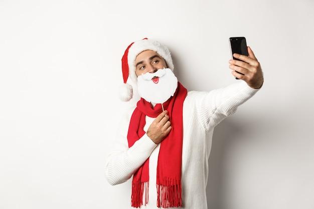 クリスマスパーティーとお祝いのコンセプト。面白い白ひげサンタマスクと帽子で自分撮りをしている若い男、携帯電話で写真のポーズ、スタジオの背景