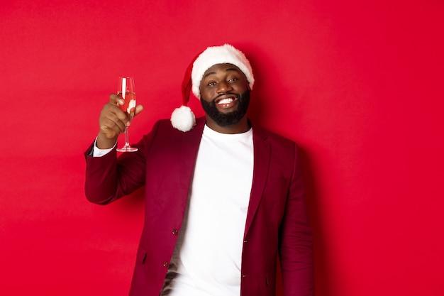 크리스마스, 파티 및 휴일 개념입니다. 쾌활한 흑인 남자는 환호성을 지르며 샴페인 한 잔을 들고 새해 복 많이 받으며 빨간 배경에 서서