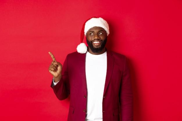 크리스마스, 파티 및 휴일 개념입니다. 쾌활한 흑인 남자가 웃고, 왼쪽 손가락을 가리키고 로고를 보고 빨간색 배경 위에 서 있습니다.
