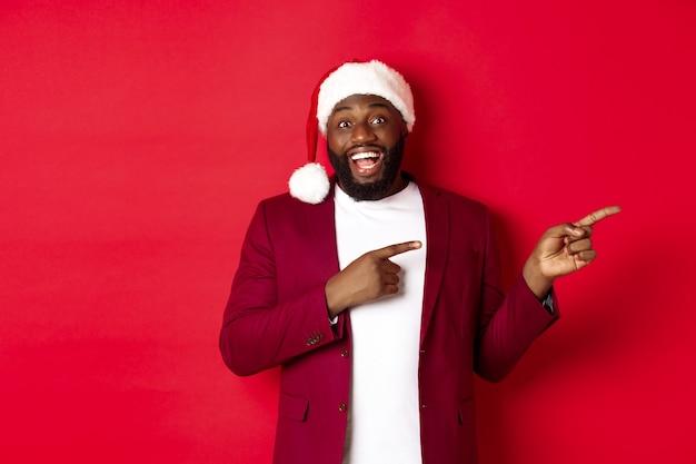 크리스마스, 파티 및 휴일 개념입니다. 쾌활한 흑인 남자가 웃고, 손가락을 오른쪽으로 가리키고, 광고를 보여주며, 빨간색 배경 위에 서 있습니다.