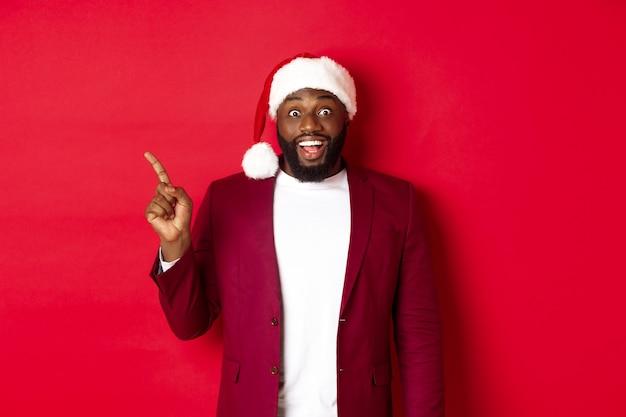 크리스마스, 파티 및 휴일 개념입니다. 흥분하고 즐거운 흑인 남자가 왼쪽으로 손가락을 가리키고 웃고, 로고를 보여주고, 빨간색 배경 위에 서 있습니다.