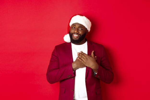 クリスマス、パーティー、休日のコンセプト。サンタの帽子をかぶった感謝の気持ちを込めて、心に手をつないで、笑顔で、感動し、赤い背景に立って、ありがとうと言っています。