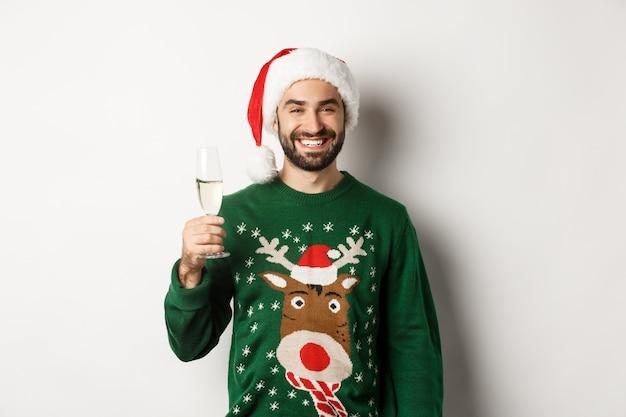 크리스마스 파티와 휴일 개념입니다. 산타 모자와 웃긴 스웨터를 입은 잘생긴 수염난 남자, 샴페인을 마시고 새해를 축하하는 흰색 배경