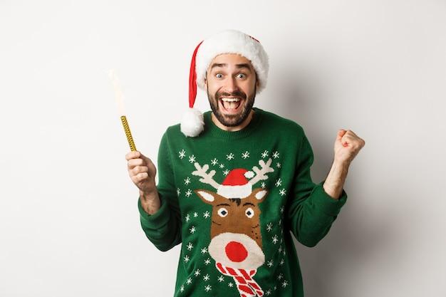 크리스마스 파티와 휴일 개념입니다. 수염을 기른 잘생긴 남자는 기뻐하고 파티 불꽃놀이를 들고 산타 모자를 쓰고 새해, 흰색 배경을 축하합니다.