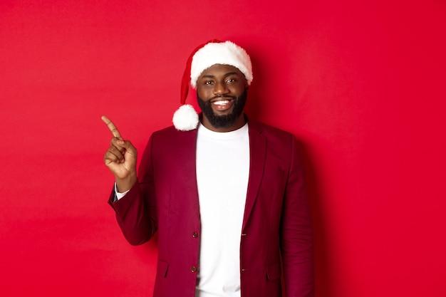 크리스마스, 파티 및 휴일 개념입니다. 산타 모자를 쓴 잘생긴 흑인 남자가 왼쪽으로 손가락을 가리키며 광고를 보여주고 빨간색 배경 위에 행복하게 서 있다