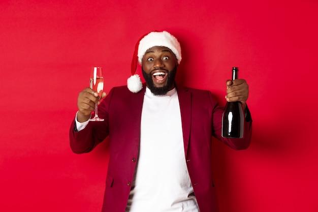 クリスマス、パーティー、休日のコンセプト。シャンパングラスを上げて笑顔、新年を祝う、赤い背景のサンタ帽子をかぶったハンサムな黒人男性。