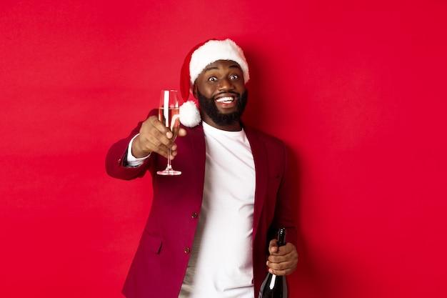 クリスマス、パーティー、休日のコンセプト。シャンパングラスを上げて、トーストと言って、新年を祝って、赤い背景のサンタ帽子をかぶったハンサムな黒人男性。