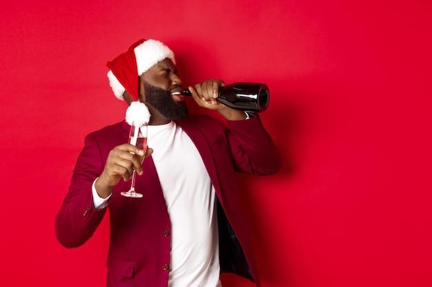 크리스마스, 파티 및 휴일 개념입니다. 산타 모자를 쓴 젊은 흑인 남성이 병에서 샴페인을 마시고 새해 축하 행사에 술에 취해 빨간 배경 위에 서 있는 이미지