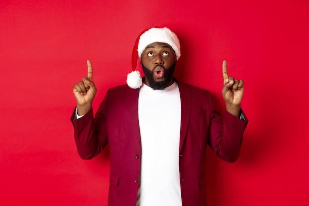 Рождество, вечеринка и праздничное понятие. впечатленный темнокожий мужчина в новогодней шапке, указывая пальцами вверх, говорит «вау» и смотрит в камеру, просматривая промо-предложение, красный фон