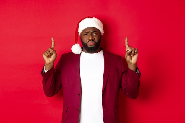 크리스마스, 파티 및 휴일 개념입니다. 비참하고 슬픈 아프리카계 미국인 남자가 손가락을 위로 가리키고 실망한 표정으로 산타 모자를 쓰고 빨간 배경을 하고 있습니다.