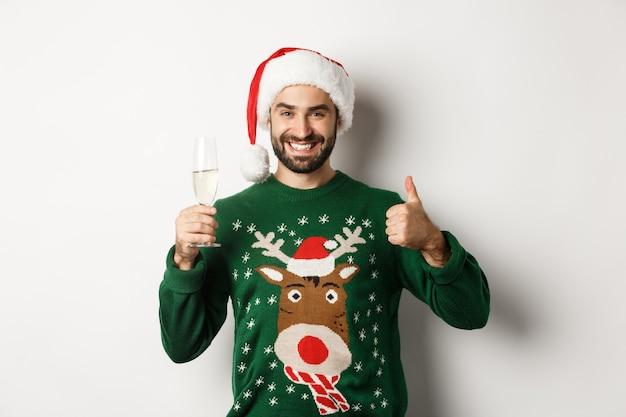 クリスマスパーティーや休日のコンセプト。親指を立ててシャンパングラスを飲みながら、白い背景の上に立って、サンタの帽子とセーターで満足している男。