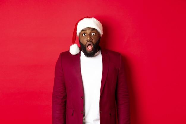 크리스마스, 파티 및 휴일 개념입니다. 충격을 받은 산타 모자를 쓴 흑인 남자는 턱을 내리고 카메라를 응시하고 빨간색 배경에 서 있습니다.