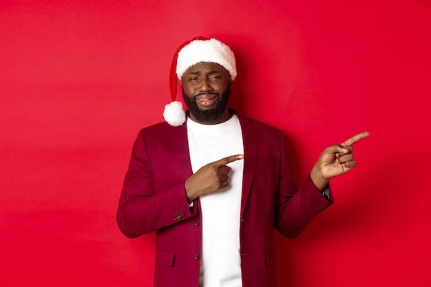 크리스마스, 파티 및 휴일 개념입니다. 회의적이고 재미없는 흑인 남성이 경멸하는 표정으로 로고를 가리키며 빨간 배경에 산타 모자를 쓰고 서 있습니다.
