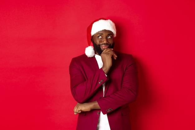 크리스마스, 파티 및 휴일 개념입니다. 새해 계획을 세우고 있는 웃고 있는 아프리카계 미국인 남자, 왼쪽 상단 모서리를 사려깊게 보고, 산타 모자, 빨간색 배경