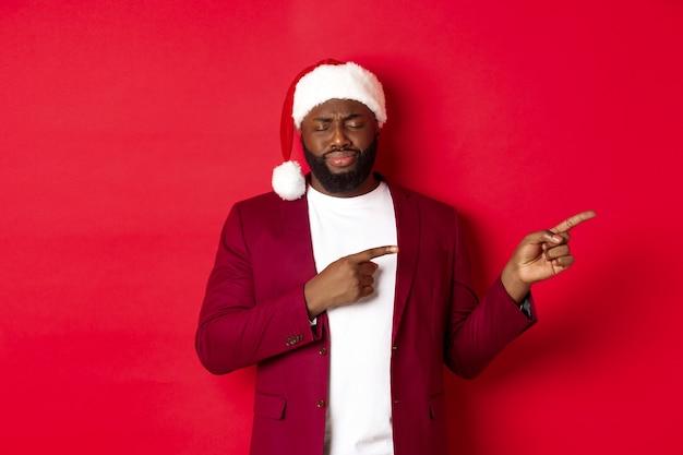 크리스마스, 파티 및 휴일 개념입니다. 우울하고 눈을 감고 한숨을 쉬고 손가락을 오른쪽으로 가리키며 빨간 배경에 산타 모자를 쓰고 서 있는 화가 난 흑인 남자