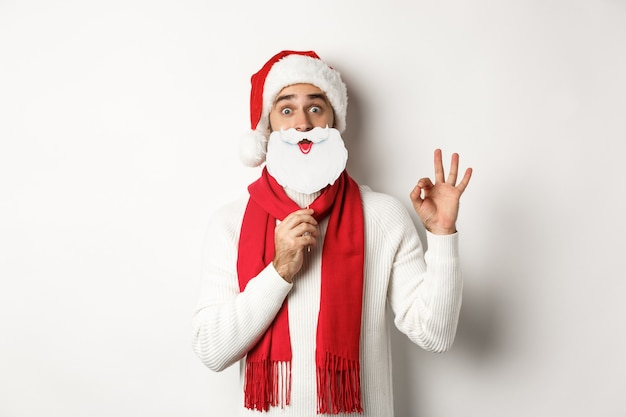 Christmas party and celebration concept. happy male model in santa claus hat and white beard mask, showing ok gesture, standing over white background