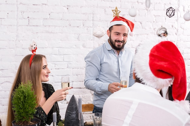飲み物と楽しみを持っているクリスマスパーティー陽気な友達
