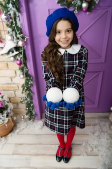 Christmas party. cheerful girl having fun christmas eve. child believe in miracle. girl little kid hold decorations. playing with snowballs. merry christmas and happy new year. decor accessory.