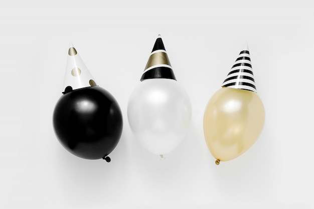 Christmas party concept. white, black and gold balloons in party hats on white background. happy new year celebration