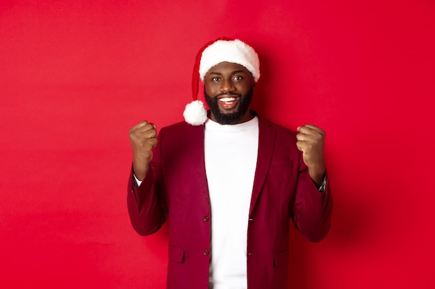 Christmas, party and holidays concept. excited black man celebrating new year, wearing santa hat, clench fists satisfied, winning and rejoicing, standing against red background.