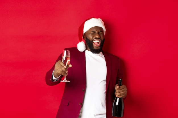 Christmas, party and holidays concept. funny drunk black man celebrating new year, laughing and having fun, holding glass and bottle of champagne, red background.