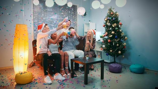색종이를 부는 행복한 젊은이들의 크리스마스 파티 시간
