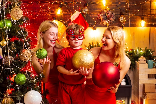 Christmas party. women red dresses celebrate christmas with little cute baby. family bonds. love peace joy. kid boy with mom or aunts sisters having fun. join celebration. christmas family fun