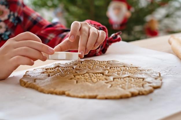 Рождественские пирожные. девушка делает имбирные пряники. деталь руки.
