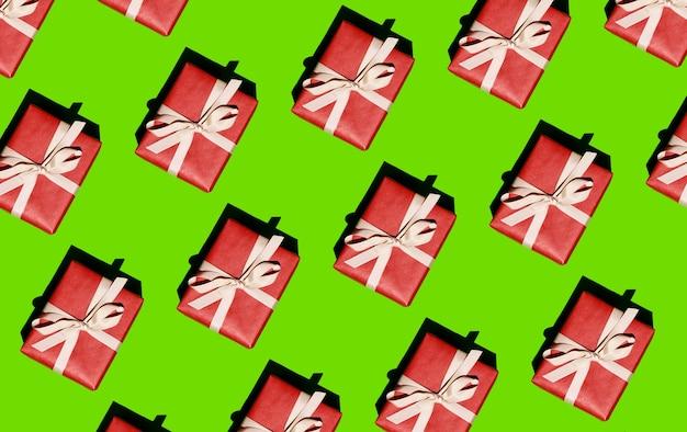 밝은 녹색 배경에 흰색 리본으로 묶인 빨간색 상자의 크리스마스 패턴