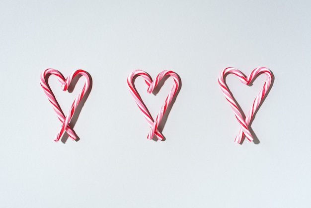 Christmas pattern of candy cane with heart shape on white background