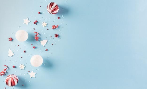 Рождественская композиция из красной ягоды, снежинки, звезд и елочного шара на пастельно-синей стене. зимняя концепция, вид сверху с копией пространства.