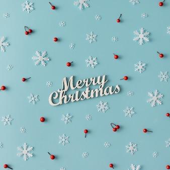 Рождественский узор из снежинок и красных ягод на синей стене. зимняя концепция. плоская планировка.