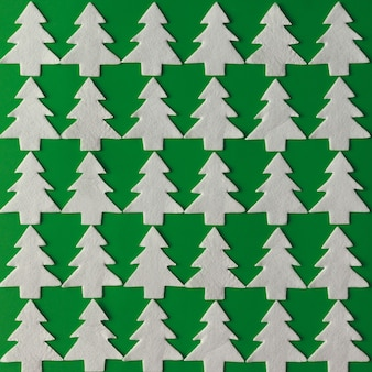Christmas pattern made of white christmas trees on green wall. flat lay. holiday concept.
