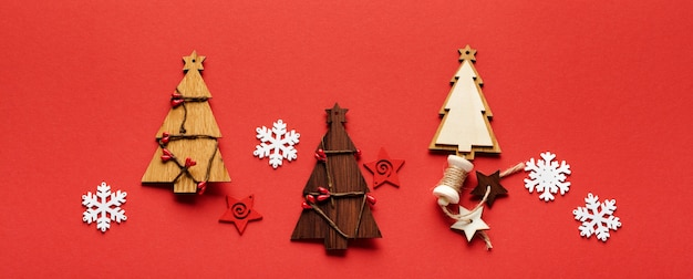 Christmas pattern made of wooden christmas fir tree toys, snowflakes and stars on red. flat lay.   banner. mock up.