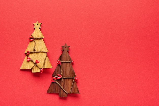 Christmas pattern made of wooden christmas fir tree toys, snowflakes and stars on red.