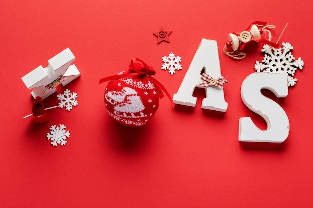 Christmas pattern made of wooden christmas letters xmas, toys, snowflakes and stars on red.