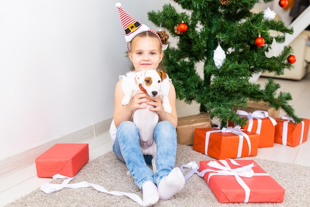 크리스마스, 애완동물, 휴일 개념 - 산타 모자를 쓴 아이와 잭 러셀 테리어 강아지.