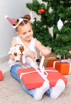 クリスマス、ペット、休日のコンセプト-ジャックラッセルテリアの子犬とサンタの帽子をかぶった子供。