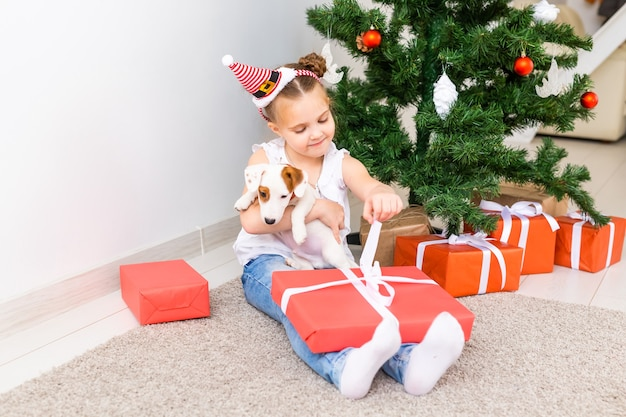 Christmas, pets and holidays concept - child in santa hat with a jack russell terrier puppy.