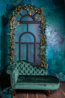 Christmas photo area with gold, blue balls and spruce on the window, vintage velvet sofa in blue.