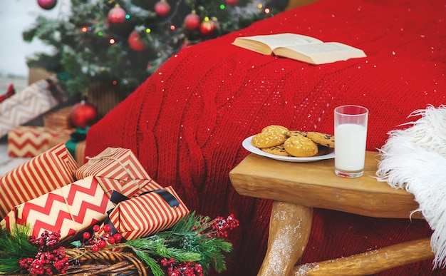Christmas photo book with cookies and a glass of milk on the bed. selective focus.