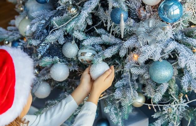 Christmas photo child decorates a christmas tree