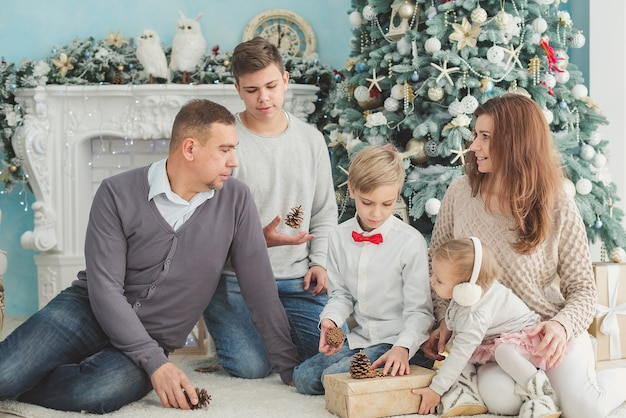 Christmas photo of large family. joy and happiness concept. portrait of large family gathering. sitting on floor, getting gifts, fir tree, fun joy.