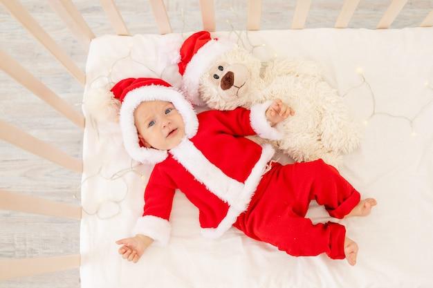 サンタクロースの帽子のおもちゃで自宅のベビーベッドで横になっているサンタ衣装の赤ちゃんのクリスマス写真