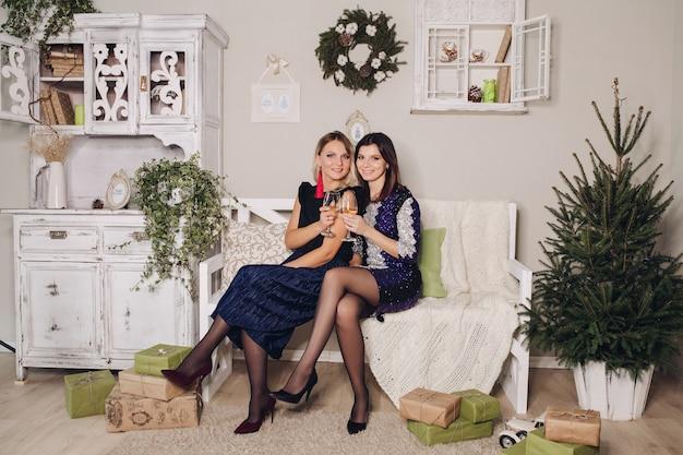 イブニングドレスの美しいガールフレンドのクリスマスの写真は贈り物に囲まれています