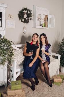 Рождественские фото красивых подружек в вечерних платьях в окружении подарков