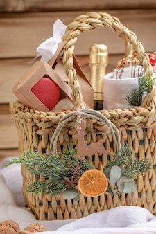Christmas picnic basket with champagne, sweet bread, macaroons and christmas ornaments.