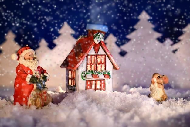 冬の夜の家の近くのサンタとバニーのクリスマス写真