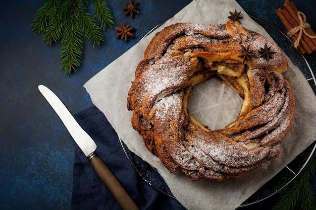 어두운 오래 된 콘크리트 또는 돌 배경에 계피와 가루 설탕과 크리스마스 파이 롤