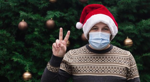 Рождественский кусок. крупным планом портрет человека в шляпе санта-клауса, рождественском свитере и медицинской маске с эмоциями. на фоне елки. коронавирус пандемия